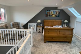 Bedroom loft conversion with wooden bed and painting on the wall