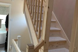 Hallway with bathroom and new wooden staircase with spindles