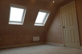 Newly plastered loft conversion with door and architrave