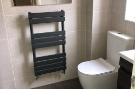 Towel radiator on cream wall tiles in bathroom