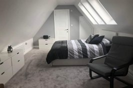 Bedroom conversion with furniture and natural light shining in