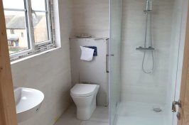 Newly built bathroom with white floor tiles