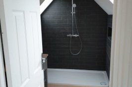 Bathroom with black tiles and wooden floor