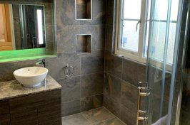 Bathroom conversion with walk in shower and grey tiles
