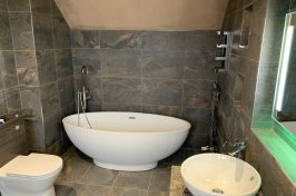 Luxury bathroom conversion with grey tiles and white suite